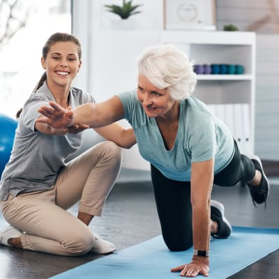 A woman doing a fitness routine with an instructor at Milestone Retirement Communities