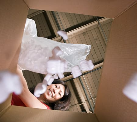 Woman packing a box to be stored at Bay Area Self Storage