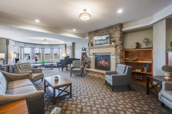Cozy resident gathering area with fireplace and large windows at Arbor Glen Senior Living in Lake Elmo, Minnesota