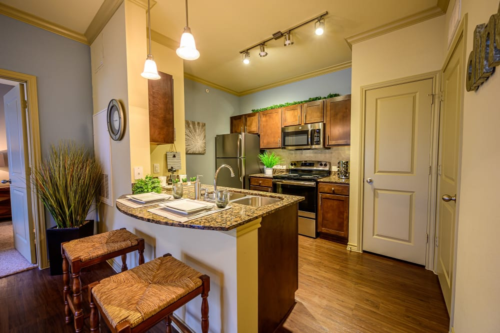 Open concept layout with bar stools and hardwood floors at Pecan Springs Apartments in San Antonio, Texas