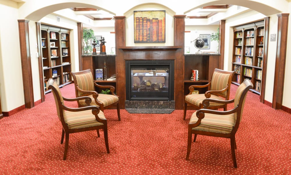 Gorgeous library with fireside seating at Ashwood Meadows Gracious Retirement Living in Johns Creek, Georgia