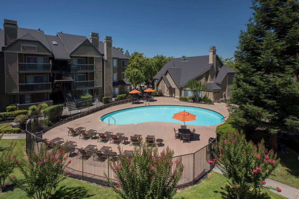 Spacious sundeck with table and chairs next to a swimming pool at Mill Springs Park Apartment Homes in Livermore, California