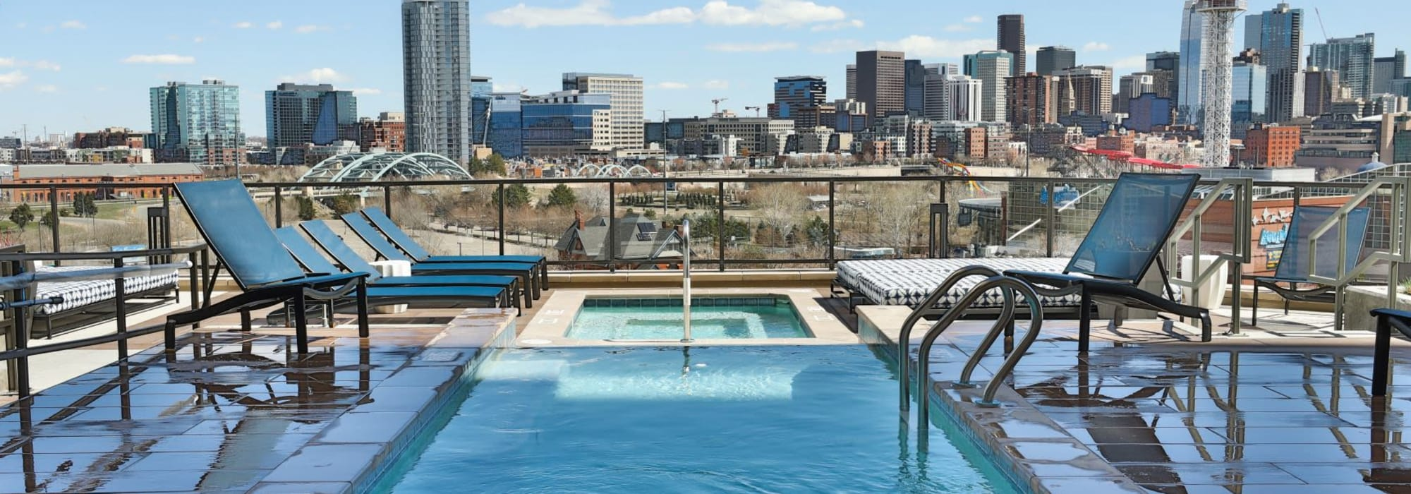 Resort-style swimming pool with shaded lounge seating nearby at The Alcott in Denver, Colorado