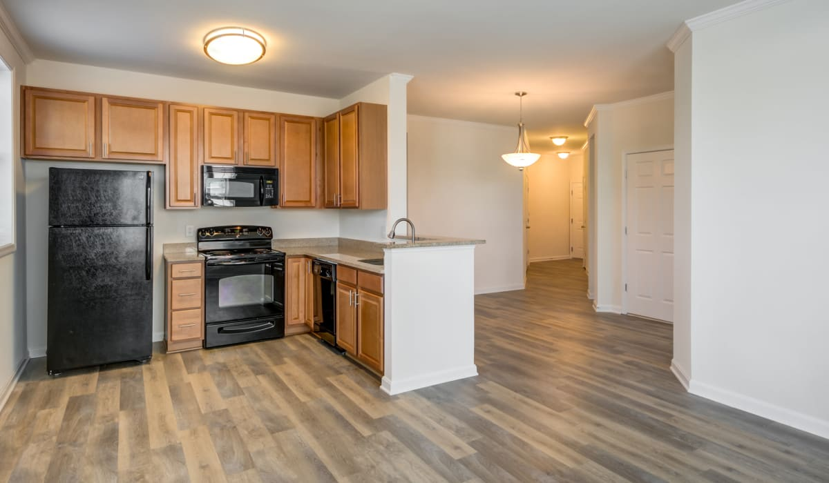 A spacious kitchen with wood-style flooring at Manassas Station Apartments in Manassas, Virginia