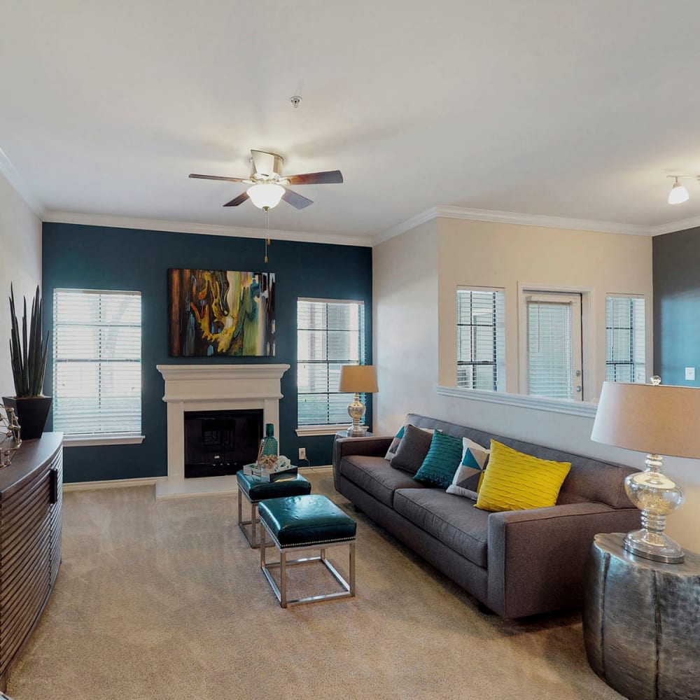 Fireplace and plush carpeting in the living area of a model home at Oaks Riverchase in Coppell, Texas