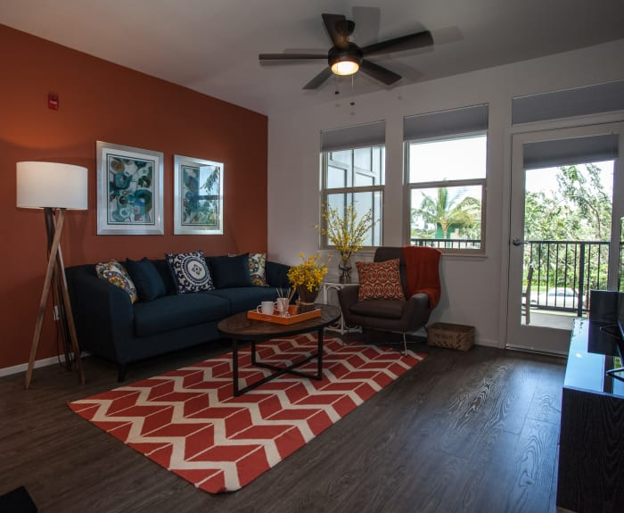 Living room with hardwood floors and ceiling fan at Kapolei Lofts in Kapolei, Hawaii