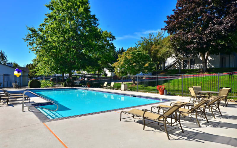 Seating near the swimming pool on a sunny day at Wellington Apartment Homes in Silverdale, Washington
