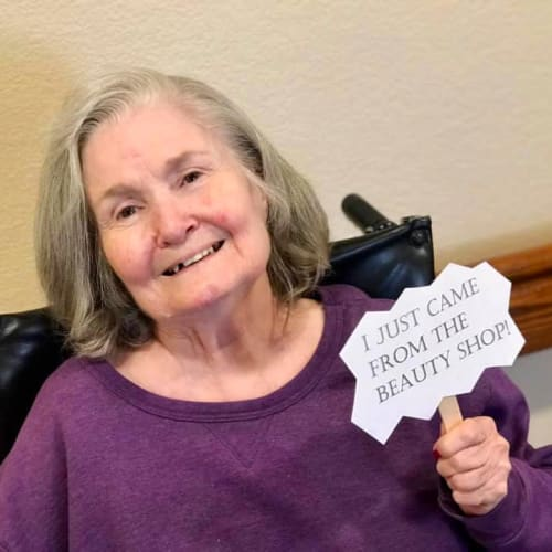 A Resident in a wheelchair holding a small sign that says 'I just came from the beauty shop!' at Oxford Glen Memory Care at Carrollton in Carrollton, Texas