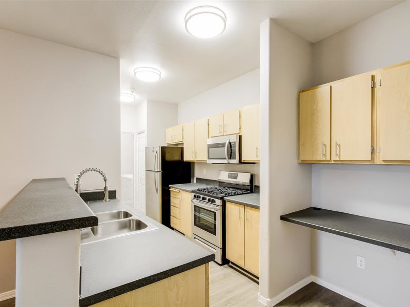 Beautiful white appliances with a stainless-steal sink at Capitol Place Apartments in West Sacramento, California