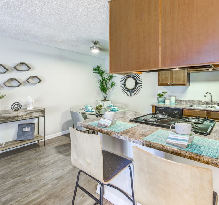 Beautiful hardwood flooring and granite countertops in the kitchen and dining areas of a model home at Sofi Poway in Poway, California