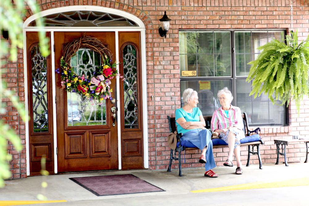 Two residents sitting outside talking at Providence Assisted Living.