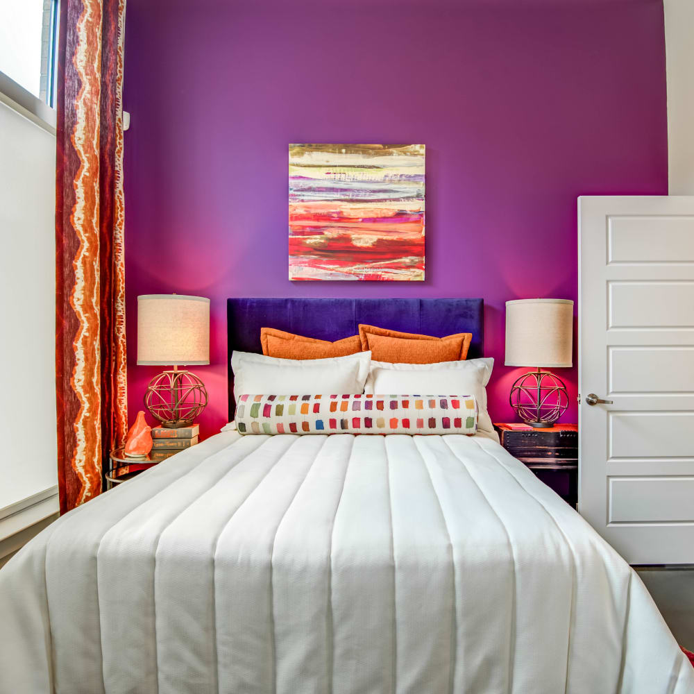 Master bedroom with purple accent at Mercury NoDa in Charlotte, North Carolina
