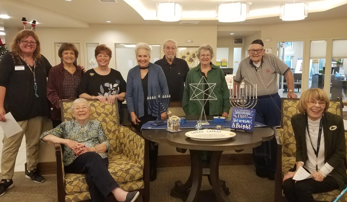 residents taking a photo with staff at Merrill Gardens at ChampionsGate in ChampionsGate, Florida