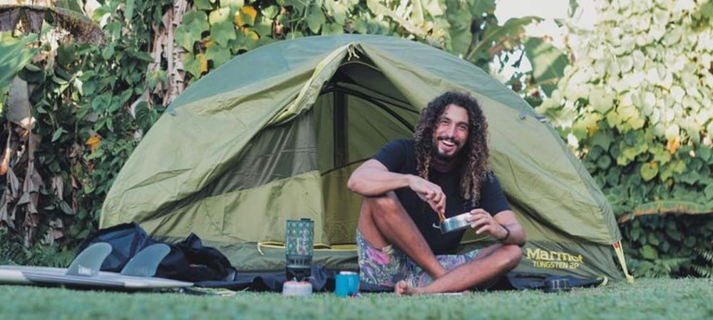 Man sitting next to tent with gear