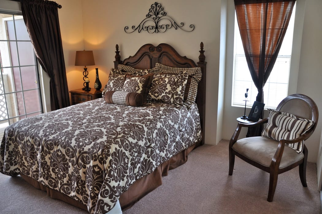 Luxury bed and chair in our bedroom at The Crest Apartments in El Paso, Texas