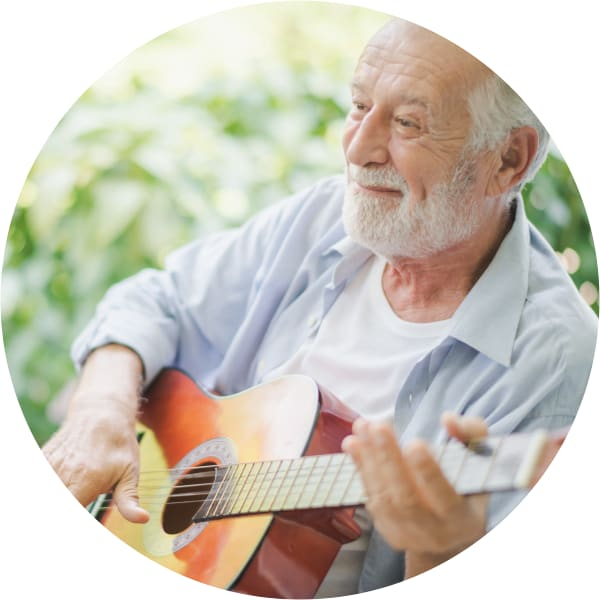 Resident sitting outside playing an acoustic guitar at a Oxford Senior Living community