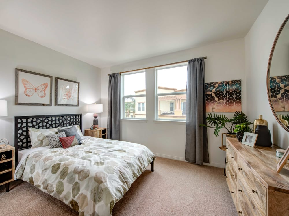 Beautifully decorated bedroom with plush carpeting and draped windows in a model home at Sofi at Topanga Canyon in Chatsworth, California