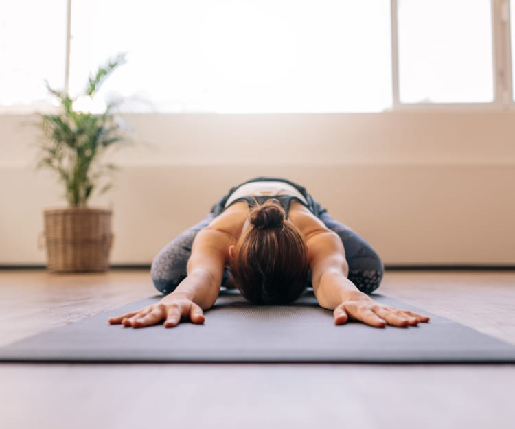 Resident doing yoga in the fitness center at Haven Warner Center in Canoga Park, California