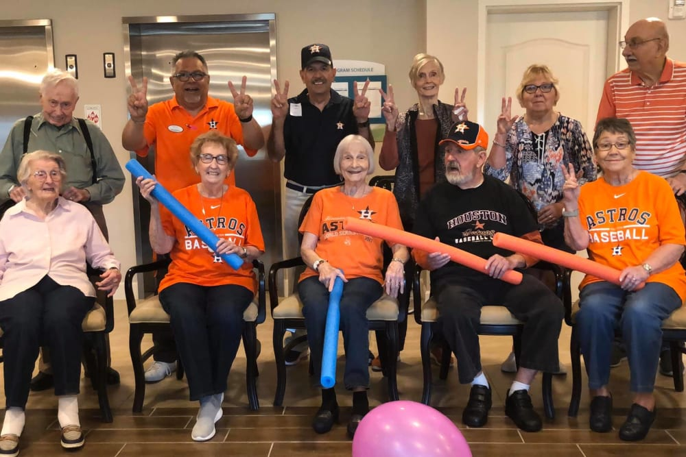 Residents and staff pose for a picture representing a baseball team at Inspired Living at Sugar Land in Sugar Land, Texas