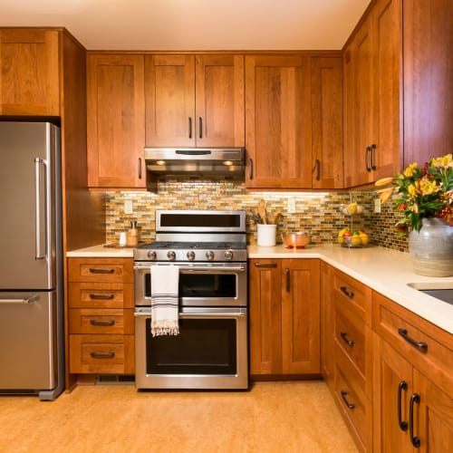 Gourmet kitchen with rich wood cabinetry in a model home at Olympus Katy Ranch in Katy, Texas