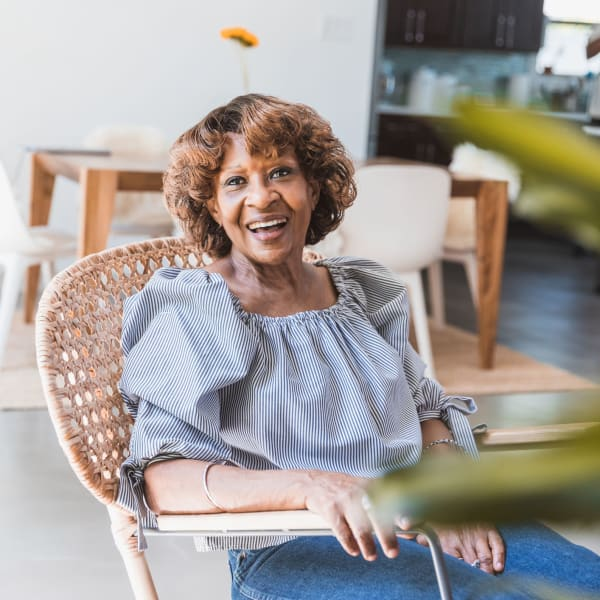 A resident smiling at Pacifica Senior Living Menifee in Sun City, California.