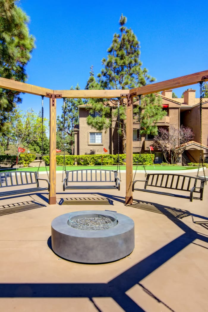 Exterior Amenity Area Fire-Pit Surrounded by swings and putting green in the background at Sierra Del Oro Apartments in Corona