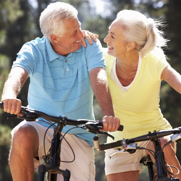 Resident couple riding bikes near Olympus Falcon Landing in Katy, Texas