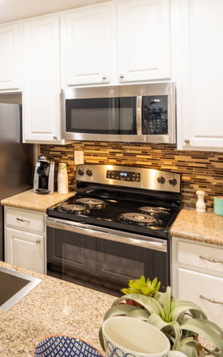 Modern kitchen with sleek, stainless-steel appliances in a model home at Haven Warner Center in Canoga Park, California