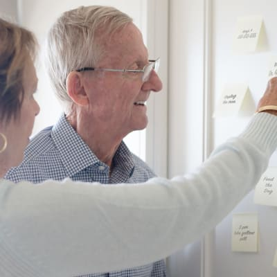 Resident looking at to-do stickynotes with a caretaker at York Gardens in Edina, Minnesota