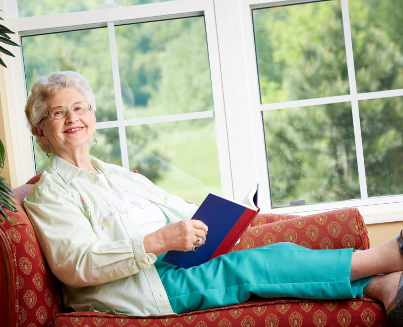 Resident reading by a bright window at Deer Crest Senior Living in Red Wing, Minnesota