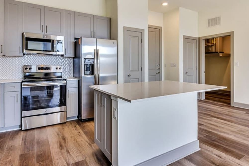 Wood floor kitchen with island bar seating at Seville Uptown in Dallas, Texas