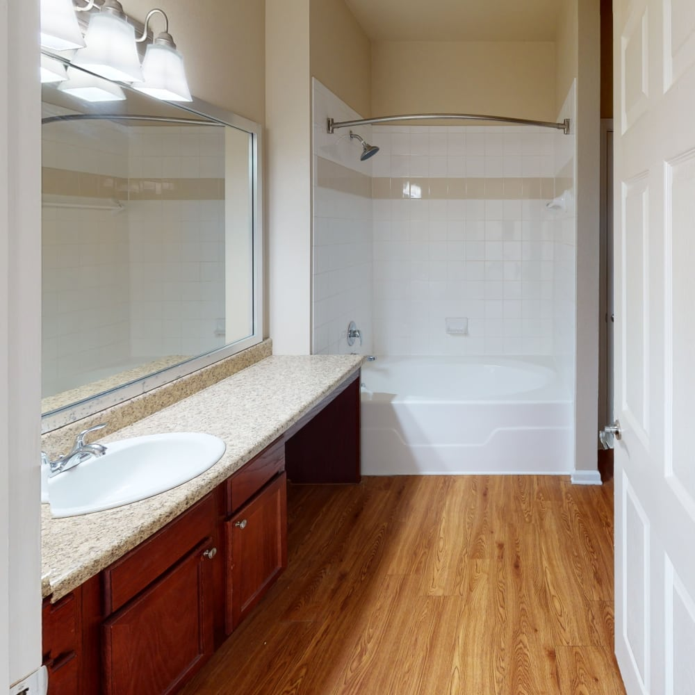 large bathtub and large vanity mirror in a townhome's bathroom at Oaks Estates of Coppell in Coppell, Texas