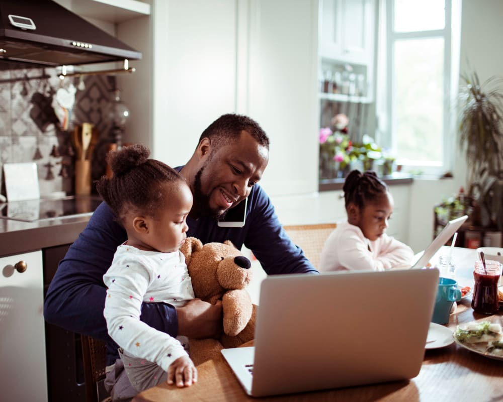 Resident working from home with his children at Clocktower Mill and Velvet Mill Apartments in Manchester, Connecticut