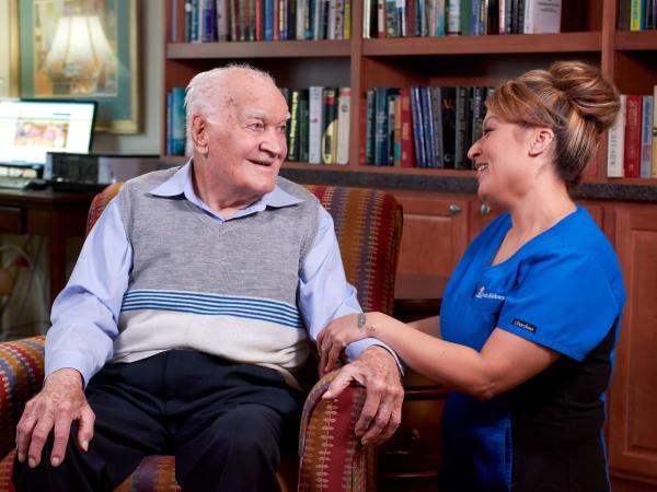 Resident enjoying a conversation with a caretaker at Las Palomas Senior Living in Mesa, Arizona