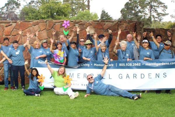 Staff and residents pose in front of a sign at Merrill Gardens at Santa Maria in Santa Maria, California.
