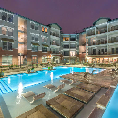 Gorgeously designed swimming pool lit up in the evening at Olympus Las Colinas in Irving, Texas