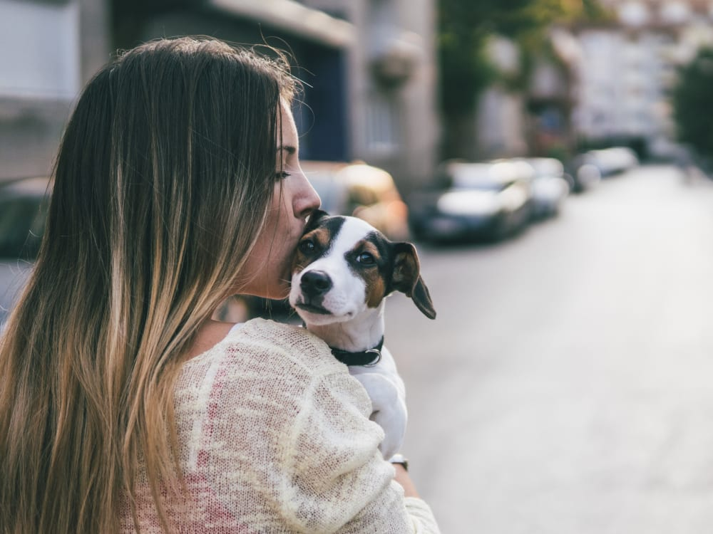 Resident holding her puppy up for a photo opportunity at Haven Apartment Homes in Kent, Washington