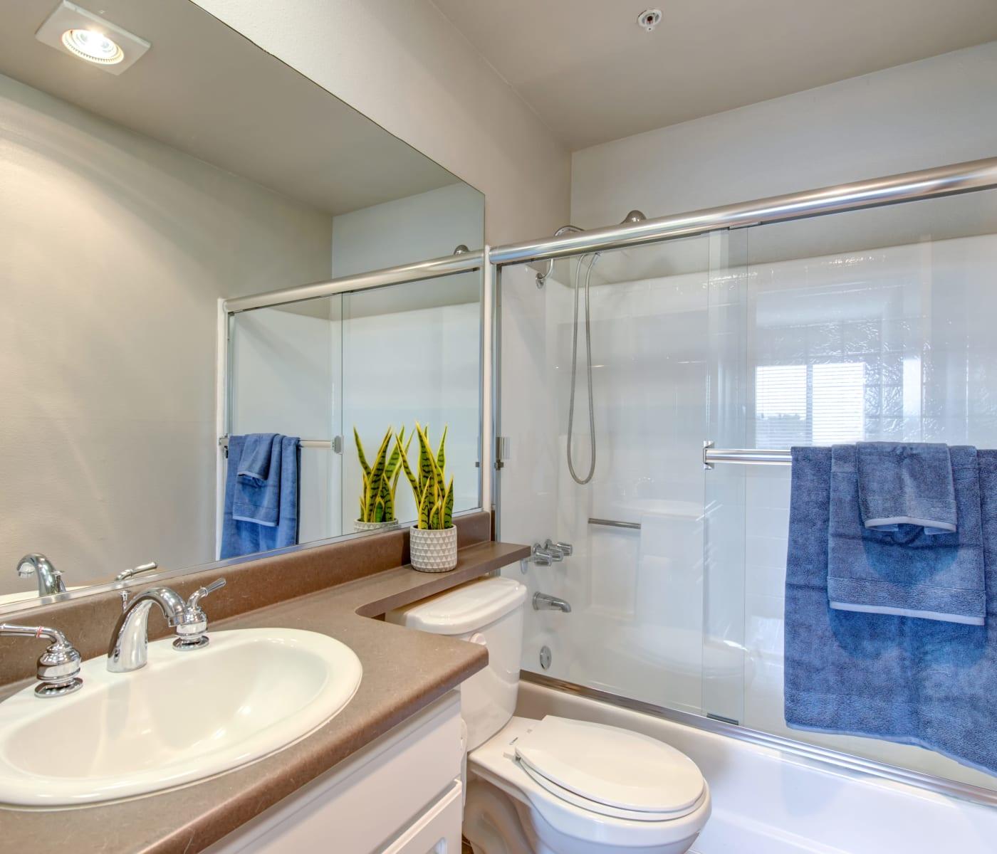 Modern bathroom with wood-style cabinetry in a model home at Vue at Laurel Canyon in Valley Village, California