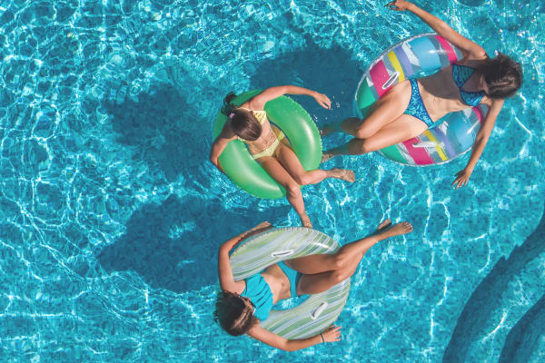 Residents floating in the pool at Panther Effingham Parc Apartments in Rincon, GA