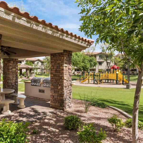 Covered Ramada with gas grills and overlooking playground at San Hacienda in Chandler, Arizona