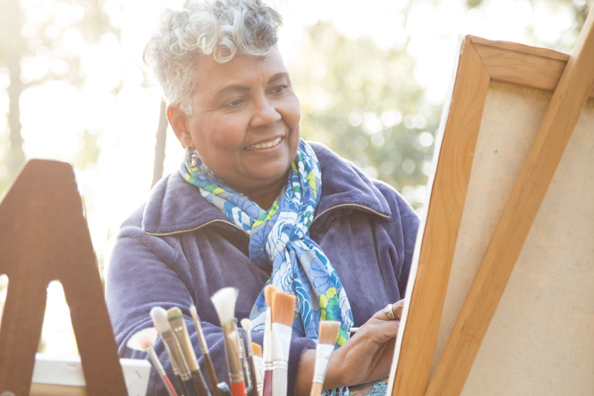 Resident painting a picture on an easel at Chandler's Square Retirement Community in Anacortes, Washington