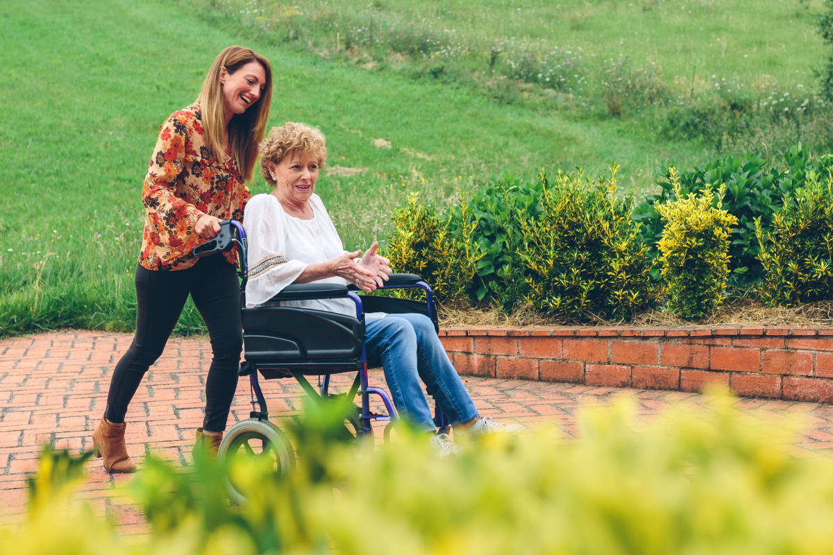 A resident in a wheel chair with a young woman assisting her at Brightwater Senior Living of Tuxedo in Winnipeg, Manitoba
