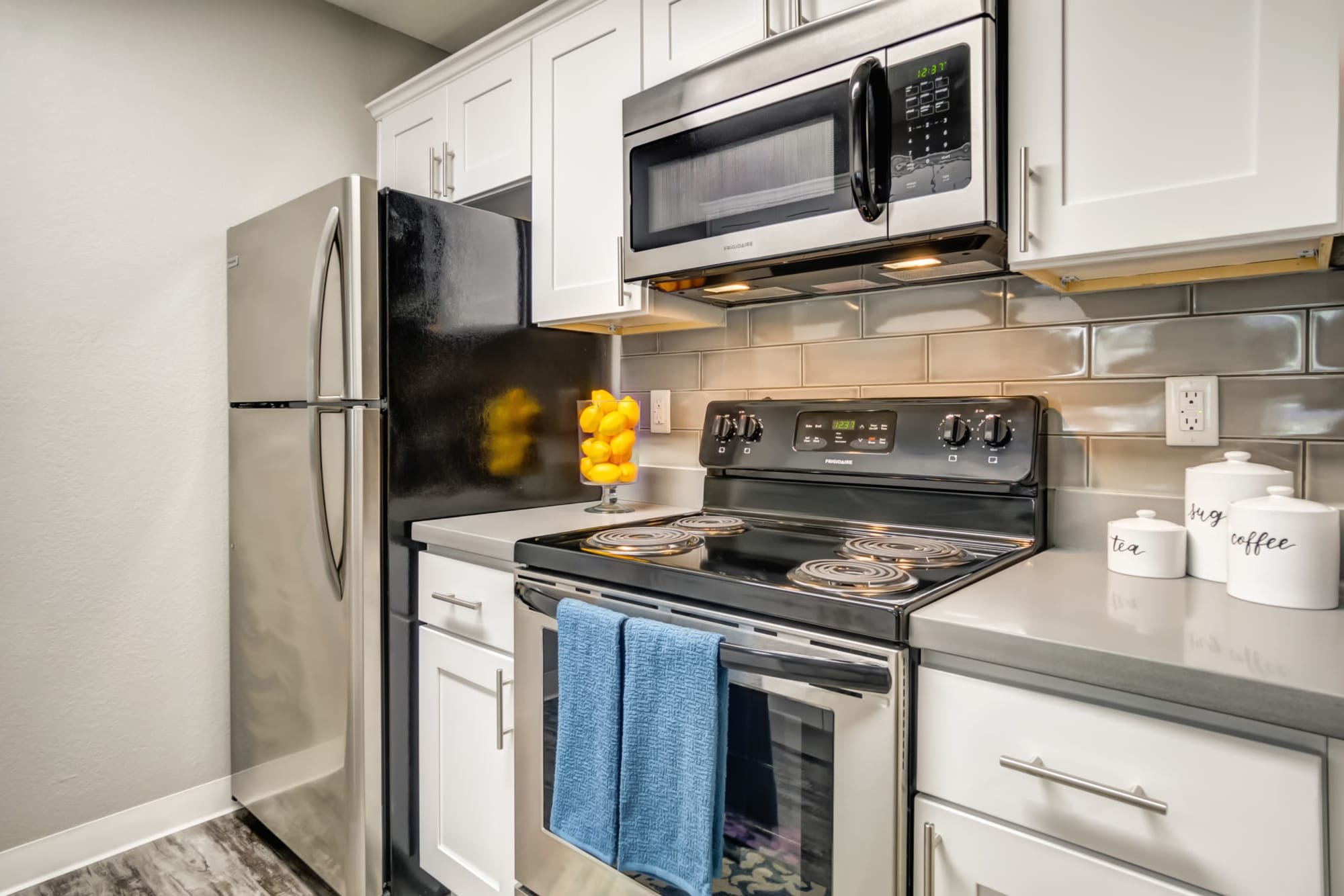 Renovated White Cabinetry Kitchen with Stainless Steel Appliances at Serramonte Ridge Apartment Homes
