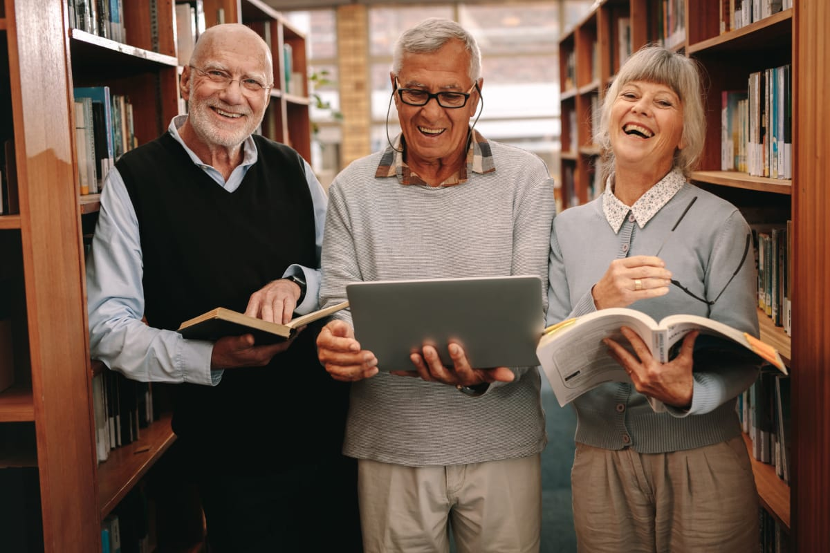 A group of residents in the library near Claiborne Senior Living.