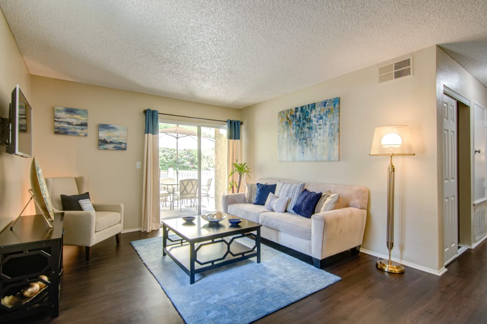 Living room with wood-style flooring at Lakeview Village Apartments in Spring Valley, California