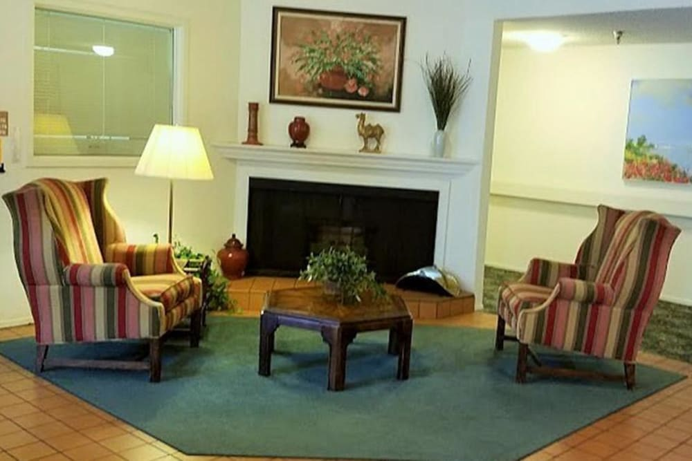 Fireplace with comfy chairs to sit in and enjoy the warmth at Leisure Manor Senior Living in Sacramento, California