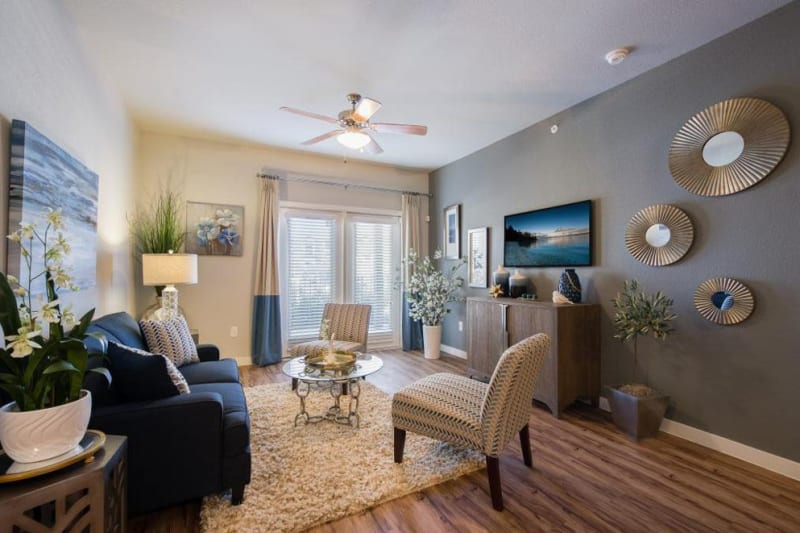 Large living room with area rug and ceiling fan at Verandas at Alamo Ranch in San Antonio, Texas