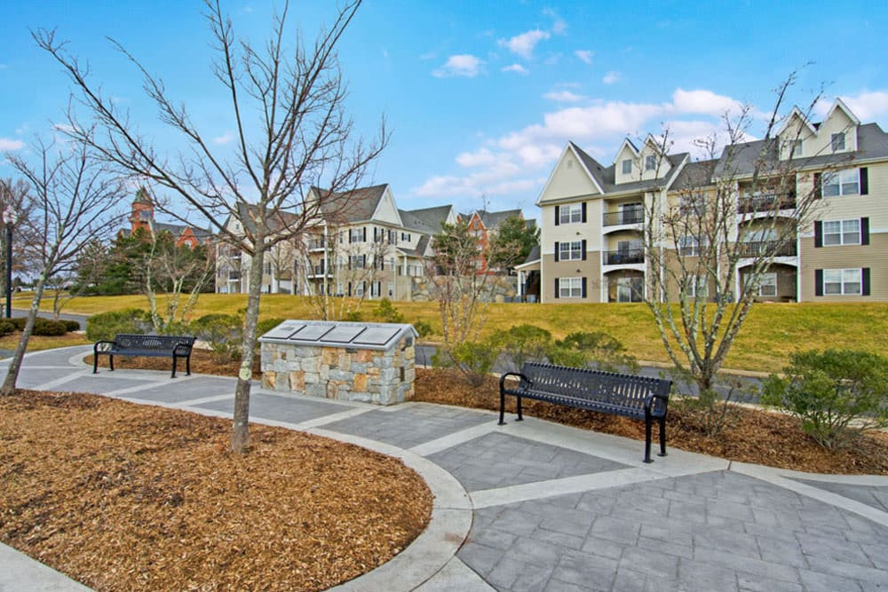 Walking paths with apartment in the distance across large grassy field at Bradlee Danvers in Danvers, Massachusetts