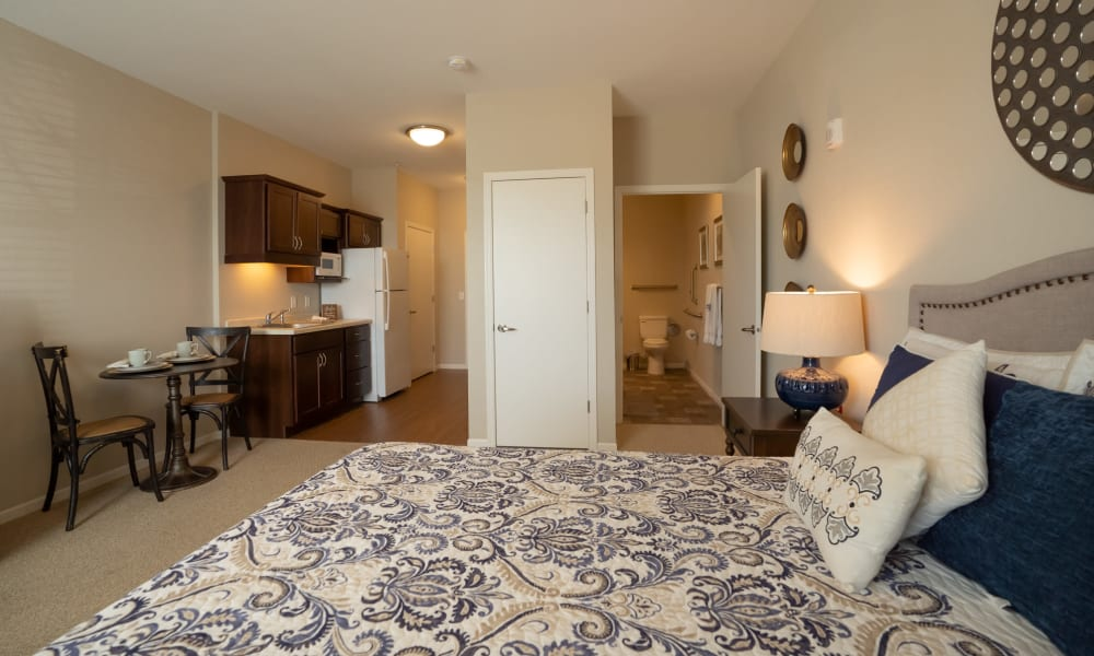 Senior living apartment suite with bed, bath, and kitchen at The Sanctuary at St. Cloud in St. Cloud, Minnesota