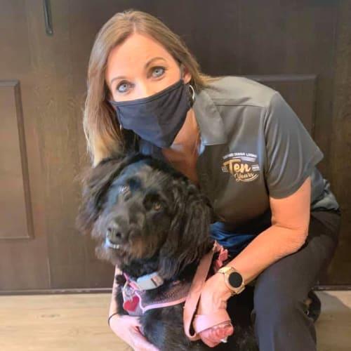 Caretaker kneeling with a black dog at Oxford Villa Active Senior Apartments in Wichita, Kansas